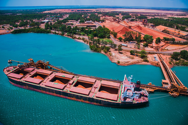 Ship being loaded at Rio Tinto Weipa operations with bauxite stockpiles in the background.